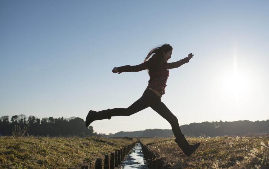 Una ragazza salta un fosso. Donna, giovani, coraggio, salto