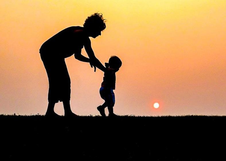 Una mamma aiuta il figlio ad imparare a  camminare